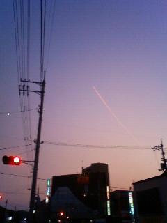 上昇するピンクの飛行機雲